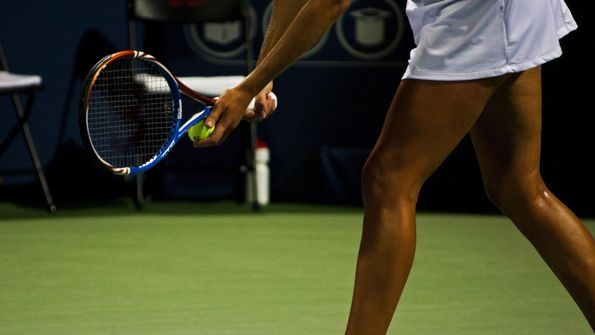 A pro tennis player getting ready to serve the ball